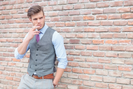casual young man leaning on a brick wall and smoking a cigarette while holding a hand in his pocket and looking away from the camera photo