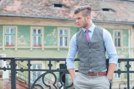 casual young man posing outdoor on a bridge with his hands in his pockets and looking to his side, away from the camera photo