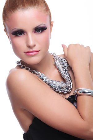 closeup of a young beauty woman holding a hand on her opposite shoulder and looking at the camera. on white background photo