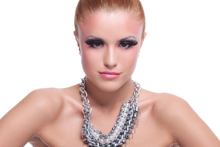 closeup of a young beauty woman with fancy necklace looking at the camera. on background photo
