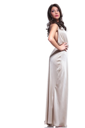 full length photo of a young beauty woman looking back, over her shoulder with her hands on her hips. isolated on white background photo