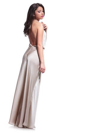 touch down: full length photo of a young beauty woman touching her shoulder while looking down, away from the camera. isolated on white background