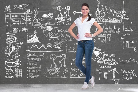 delays: full length picture of a young casual woman standing with her hands on her hips in front of a background full of sketches and charts and smiling for the camera Stock Photo