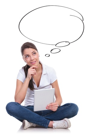 casual young woman sitting with legs crossed and looking up at a speech bubble pensively while holding her tablet. isolated on white background