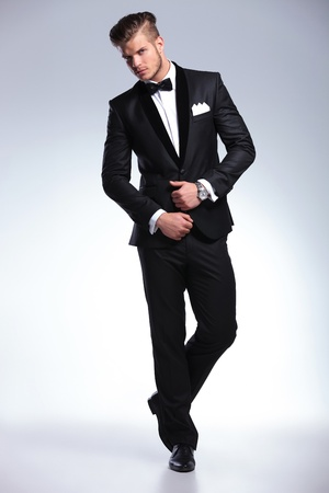 tuxedo: full length photo of an elegant young fashion man in tuxedo looking at the camera while holding his hands on his jacket. on gray background