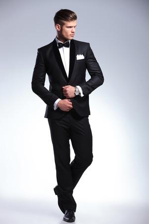 カメラから離れて、彼の側に見ながら彼のタキシードを調整する、エレガントなファッションの若い男の完全な長さの画像。灰色の背景に