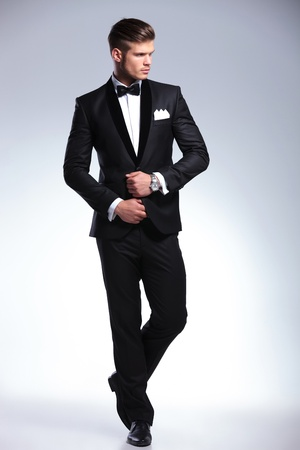 tux: full length picture of an elegant young fashion man adjusting his tuxedo while looking to his side, away from the camera. on gray background