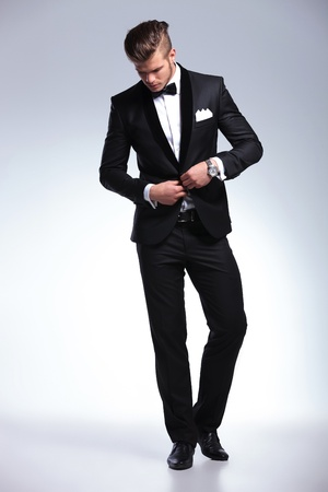 man in tuxedo: full length picture of an elegant young fashion man in tuxedo buttoning his jacket while looking down, away from the camera. on gray background