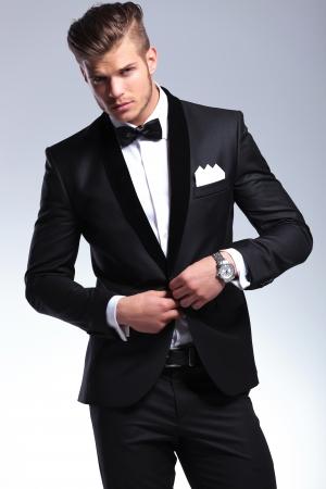 당신을 찾고있는 동안 그의 재킷 단추를 끼우는 턱시도 우아한 젊은 패션 남자. 회색 배경에