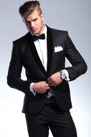 tuxedo: elegant young fashion man in tuxedo buttoning his jacket while looking at you. on gray background