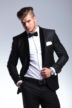 unbuttoned: elegant young fashion man in an unbuttoned tuxedo looking at the camera. on gray background Stock Photo