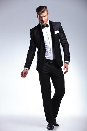 カメラを見ながら、タキシードのポーズでエレガントなファッションの若い男の完全な長さの画像。灰色の背景に