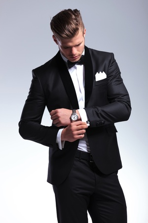 arrange: elegant young fashion man in tuxedo looking at his cufflinks while fixing them. on gray background