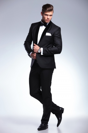 full suit: full length portrait of an elegant young fashion man in tuxedo looking at the camera while holding his hands on his jacket and a leg behind the other. on gray background