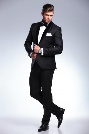tuxedo man: Ritratto di lunghezza completa di un elegante moda giovane uomo in smoking guardando la telecamera mentre si tiene le mani sulla sua giacca e una gamba dietro l'altra. su sfondo grigio