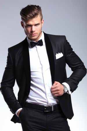 unbuttoned: portrait of an elegant young fashion man in tuxedo holding a hand in his pocket and the other on his unbuttoned jacket while looking at the camera. on gray background