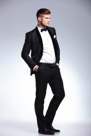 full length picture of an elegant young fashion man in unbuttoned tuxedo with his hands in his pockets and looking away from the camera.on gray background photo