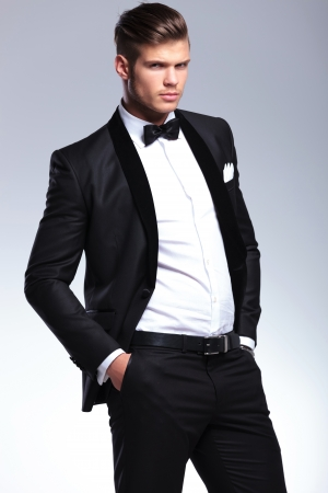 elegant young fashion man in unbuttoned tuxedo holding his hands in his pockets while looking at the camera. on gray background photo