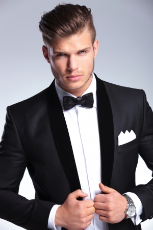 formal clothes: cutout picture of an elegant young fashion man holding both hands on his tuxedo jacket while looking at the camera. on gray background Stock Photo