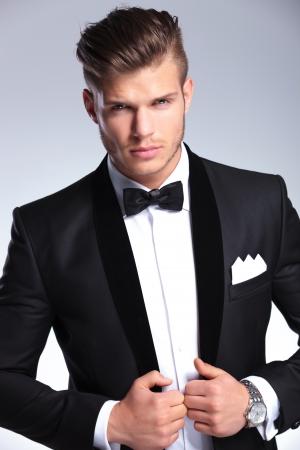 ambos: recorte la imagen de un hombre de moda joven elegante que sostiene ambas manos en la chaqueta del esmoquin mientras mira a la c�mara. sobre fondo gris Foto de archivo