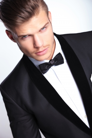 closeup cutout picture of an elegant young fashion man in tuxedo looking at the camera.on gray background photo