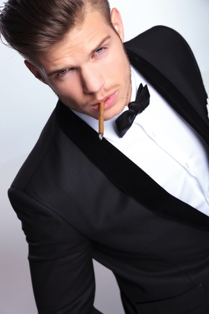 high angle view of an elegant young fashion man in tuxedo holding a lit cigar in his mouth while looking at the camera. on gray background  photo
