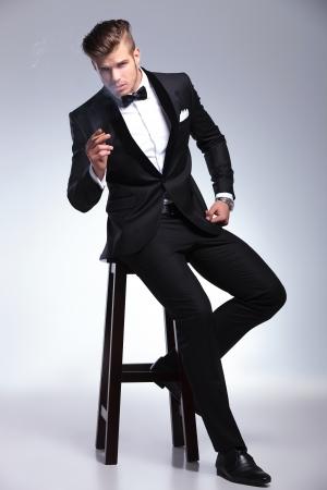 elegancki młody człowiek w smokingu moda siedzi na stołku i trzymając cygaro w ręku, patrząc na kamery. na szarym tle