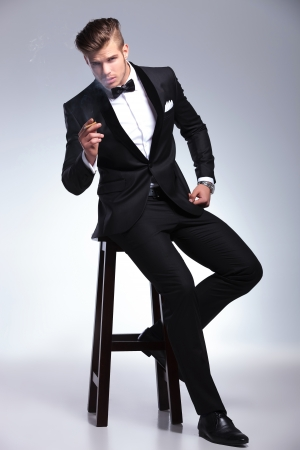 persona fumando: elegante hombre de moda joven en el smoking que se sienta en un taburete y que sostiene un cigarro en la mano mientras mira a la cámara. sobre fondo gris