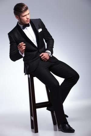 턱시도 우아한 젊은 패션 남자 카메라에서 멀리 찾고있는 동안 의자에 앉아 담배. 회색 배경에 스톡 콘텐츠