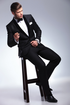 the stool: elegant young fashion man in tuxedo sitting on a chair and smoking while looking away from the camera. on gray background