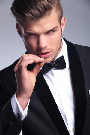 lazo negro: Primer plano de un elegante hombre de moda joven en el smoking que mira la cámara mientras se preparaba para tomar un humo de su cigarro. sobre fondo gris