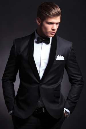 waist-up picture of an elegant young fashion man in tuxedo looking away from the camera while holding hands in pockets.on black background photo