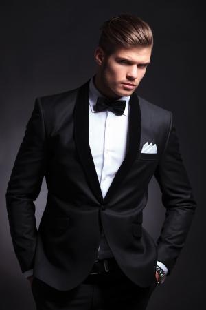 彼はポケットに手を差し伸べていると camera.on 黒い背景を探してタキシードでエレガントなファッションの若い男