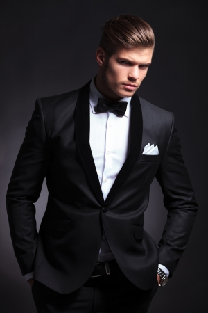 elegant young fashion man in tuxedo holding his hands in his pockets and looking to the camera.on black background photo