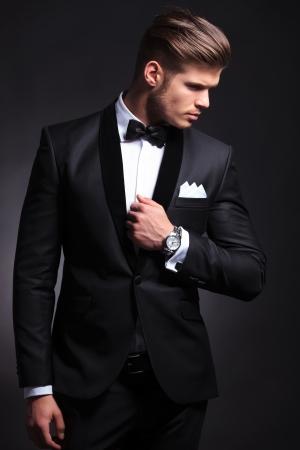 noeud papillon: élégant jeune homme de mode en smoking tenant sa main sur sa veste et en regardant sur le côté, loin de l'arrière-plan noir camera.on