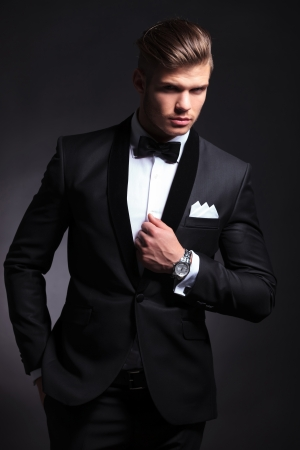 elegant young fashion man in tuxedo with a hand on his collar and the other in his pocket while looking at the camera.on black background photo
