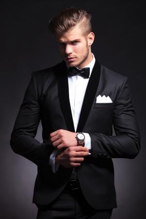 elegante hombre de moda joven en el smoking ajustando sus gemelos mientras mira a la cámara. sobre fondo negro