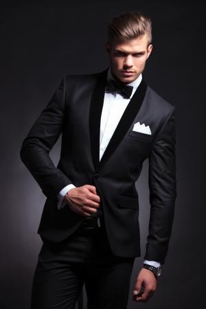 カメラを見て彼のタキシード ジャケットに手でエレガントなファッションの若い男。黒の背景に 写真素材