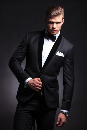 elegant young fashion man with a hand on his tuxedo jacket looking at the camera. on black background photo