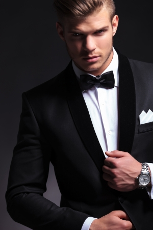 cutout picture of an elegant young fashion man fixing his tuxedo while looking at the camera.on black background photo