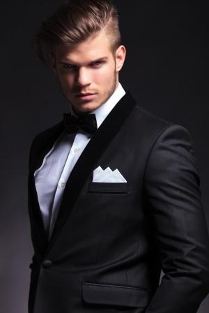 camera.on 黒い背景を見てタキシードのエレガントなファッションの若い男の肖像 写真素材