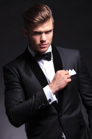 elegant young fashion man in tuxedo holding his pocket handkerchief with a hand while looking at the camera.on black background Stock Photo