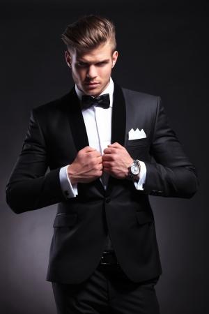 camera.on 黒い背景を見ながら彼の襟に両方彼の手を繋いでいるタキシードでエレガントなファッションの若い男 写真素材