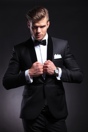 elegant young fashion man in tuxedo holding both his hands on his collar while looking at the camera.on black background Stock Photo