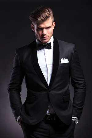 both: elegant young fashion man in tuxedo holding both his hands in his pockets while looking at the camera with a frowned expression. on black background Stock Photo