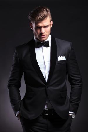 elegante: élégant jeune homme de mode en smoking tenant ses deux mains dans ses poches tout en regardant la caméra avec une expression fronça les sourcils. sur fond noir