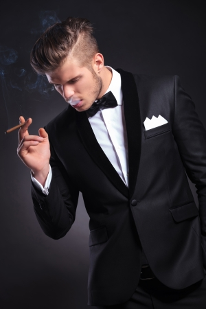 hombre fumando puro: elegante hombre de moda joven en el smoking tomar un humo y la celebración de una mano en el bolsillo mientras se mira lejos formar la cámara. sobre fondo negro Foto de archivo