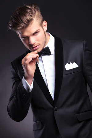 elegant young fashion man in tuxedo preparing to take a smoke from his cigarette while looking at the camera. on black background photo