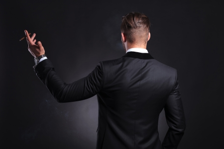 view of an elegant office: back view of an elegant young fashion man in tuxedo holding a cigar in his raised hand .on black background