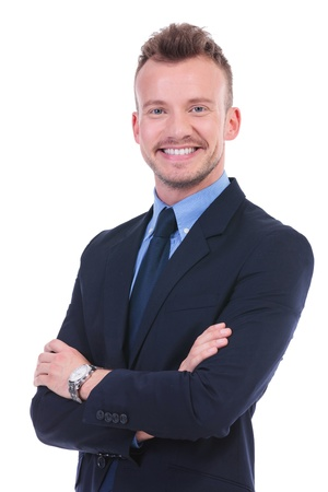 folded hands: young business man standing with his arms crossed while smiling to the camera. on white background